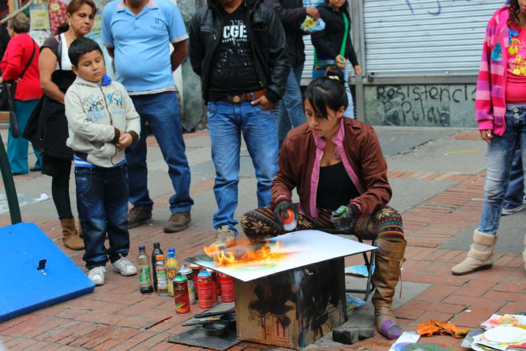 A young woman uses spray paint and fire to create art.