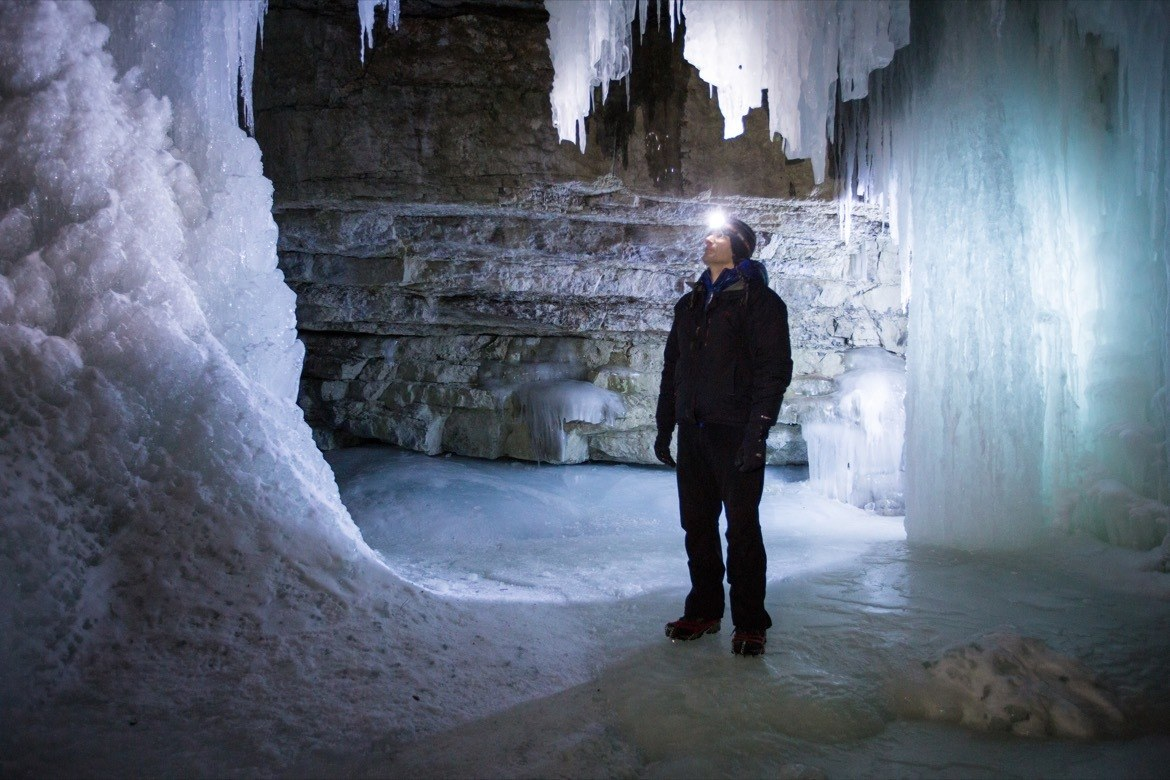 Man with head lamp ice walking at night in Maligne Canyon in Jasper National Park.